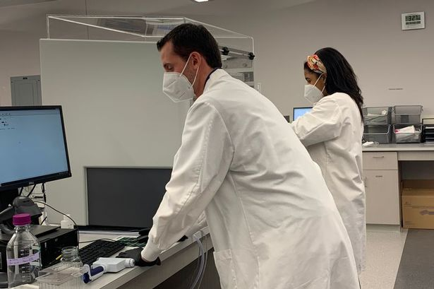 Two people in laboratory coats and masks