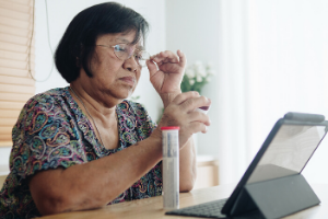 Woman looking at laptop with medicine