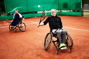 Two men in wheelchairs playing tennis on clay court
