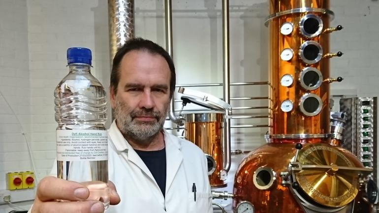 Man holding bottle of alcohol in front of distillery