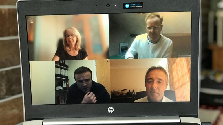 Picture of 4 people in an online meeting