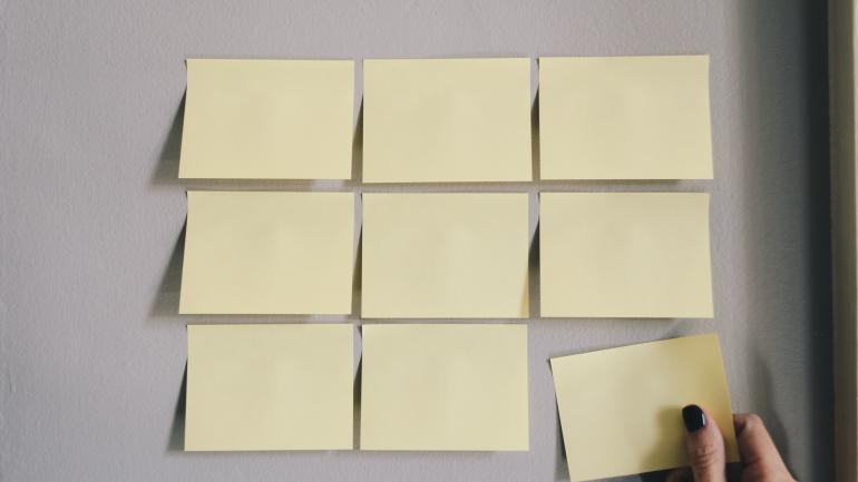 Nine yellow sticky notes on a wall